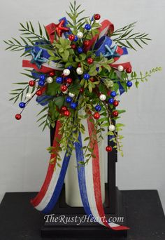 Our lantern swags are great way dress up any lantern! This swag is decorated with Red/White/Blue jute ribbon, various greens, stars, and berries.