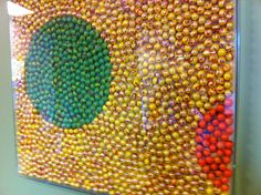 Use marbles, some glue, and a clear shadow box frame to make a geometric work of art