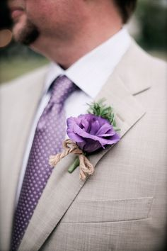 A simple boutonniere using purple lisianthus, fresh herbs, tied with twine, creating a vintage, shabby chic wedding.