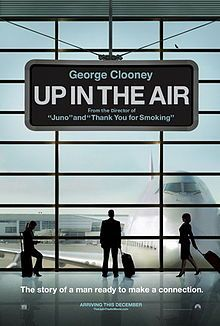 "The poster of an airport window looking onto the tarmac with a Boeing 747 at the gate. An airport sign at the top: ""George Clooney"", ""Up in ..."