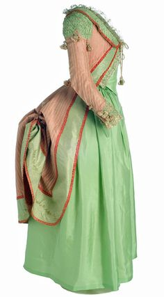 "Side view: Polonaise, Spain, 1775-1785, Salmon silk & fabric decoration with applied green silk taffeta. 5 covered cylindrical buttons at the wrist. The seams are covered by a braided cord that ends at the waist loop and tassel trimmings. Known internationally as ""the polonaise"", in Spain was known as ""Polish"". Popular during the reign of Carlos III. Spanish identity of this polonaise is in the decorative elements, such as draping shoulder pads that cover the shoulder seams. (c) Museo del…"
