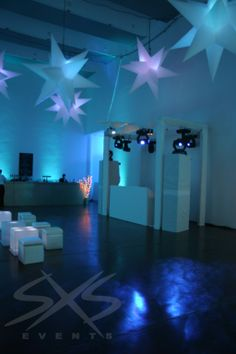 All white dressed DJ booth, with moving lights, cool blue room wash and inflatable stars.
