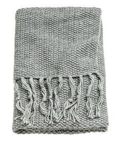 Beige. Throw in soft, moss-knit fabric with wool content. Fringe at short sides.