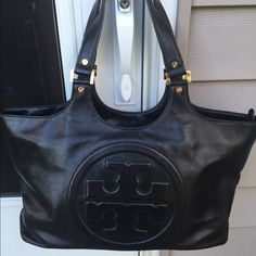 """Tory Burch Bombe Bag in Black Tory Burch Bombe Black bag Very good condition This glazed, smooth leather tote features a large logo front and center. Metal feet.  Gold hardware.   TB dust bag. Main closure is by zipper. Interior has zip pocket and 2 slip pockets. Interior shows minor wear.  9.5""""H x 14""""L x 4""""D. 8"""" strap drop.  Please enlarge all pics as this bag is preowned. Measurements are estimated. Bag is sold as is. SORRY NO RETURNS. Have a great day! Tory Burch Bags Shoulder Bags"""