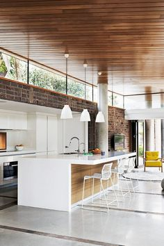 Timber clad ceiling, white lacquer kitchen, concrete floors and exposed brick.