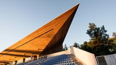 Wooden spike shelters grandstand at Estonian stadium by KAMP Arhitektid