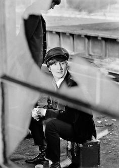 Magnum Photos - The BEATLES during filming of 'A Hard Days Night'. The Beatles film was primarily shot on a moving train. John Lennon on train platform. 1964. photo by David Hurn