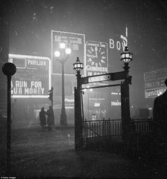 The entrance to Piccadilly underground station is visible from the lights of the neon adve...
