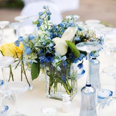 Easy Centerpieces:To create their centerpieces, Julie used different sizes of square vases and mixed hydrangea, gardenias, and yellow roses. She surrounded the arrangements with blue votives she found at Pottery Barn.