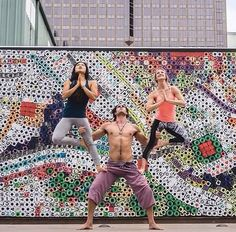 acroyoga - three person pose with two flyers doing tree pose on bases legs.
