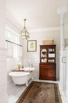 Farmhouse Bathroom Remodel Ideas. White shiplap with claw foot bathtub, brown hutch for storage, pendant light #ad #bathroom #clawfoottub #shiplap #pendantlight