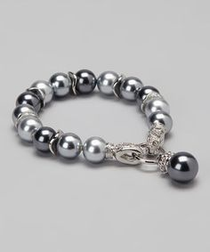 Polish off a posh ensemble with sophisticated shine. Boasting sleek silver plating and gleaming pearly beads with a convenient magnetic clasp closure, this bright bracelet is a fashionable finishing touch.