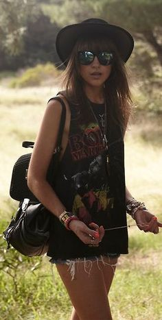 black bob marley or other artist printed sleeveless tank with low armpits, tattered and frayed denim shorts, black sunglasses, and black sun hat.