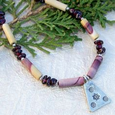 HIGH DESERT SONGS is a glorious handmade gemstone necklace designed with a Thai triangle pendant, mookaite jasper, garnet and sterling silver.  I emanates the colors of the desert from sandy yellow tans through mauves and maroons.  Carefully handmade by Catherine of Shadow Dog Designs, this stunning piece of one of a kind (OOAK) jewelry is a true desert inspiration!    The focal piece of HIGH DESERT SONGS is a lovely, rustic-looking Karen Hill Tribes handmade fine silver pendant in made in a…