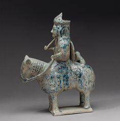 Container in the shape of a horse and rider, 12th–13th century  Iran  Composite body, underglaze-painted    H. 10 7/8 in. (27.6 cm), W. 3 in. (7.6 cm), D. 8 1/4 in. (21 cm)  Harris Brisbane Dick Fund, 1966 (66.23)