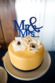 Vanilla wedding cake with gold fondant, sugar paste anemones and navy cake topper. From the Handmade Cake Company