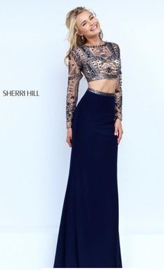7aa0b4462a41 Two-piece Sherri Hill 50097 with long sleeved embellished open back crop  top, floor length high-waist skirt with embellished waist band.