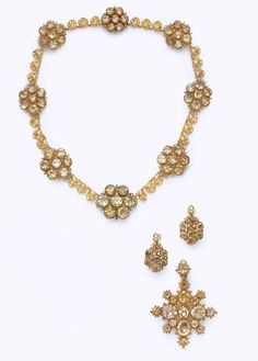 A SUITE OF ANTIQUE CITRINE AND GOLD JEWELRY   Comprising a necklace, designed as old European-cut citrine foiled-back clusters, spaced by three gold seashells; a pair of ear pendants and a pendant en suite, mounted in gold, circa 1820, ear pendant backs of a later addition, necklace 15 ins