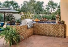 The tiled outdoor kitchen features several tile patterns, including one that borders the bottom of the walls and mimics a baseboard.