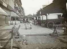 In this circa 1890 photo, a pair of girls walk east along 42nd Street in New York. Acker, Merrall and Condit wine shop delivery wagons are on the right and the C.C. Shayne Furrier sign can be seen on the roof overhead.