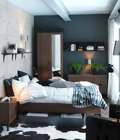 I like the light accent wall against the dark blue/grey wall. This wall paper (cement wall printed) is huge popular in Korea these days. The black wall, dark brown furniture,  white fabric and green looks perfect.