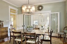 Welcoming Dutch Colonial Home in Texas. Transoms, cool sage walls, gloss white trim, dark wood furnishings for this dining room. Check out the barrel shaded chandelier.