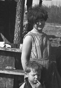1936: Twelve-year old girl of family of nine living in one-room hut built over the chassis of abandoned Ford truck in open field on U.S. Route 70 between Camden and Bruceton, Tennessee. View also shows one of the small boys in family; the girl is dressed in a meal sack.