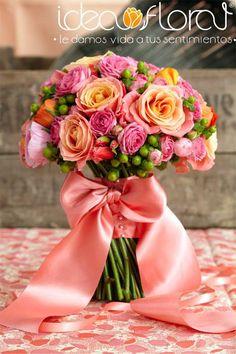 ramo de novia de rosas y mini rosas en tonos coral y rosa tenue, contrastando bellamente con hipericum en color verde