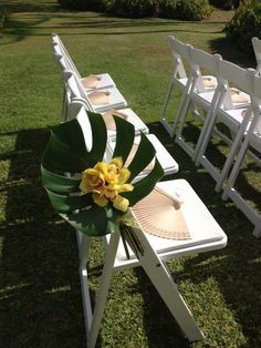 A simple pop of color with monstera leaves and orchids line the aisle with fans to help keep guest cool