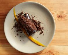"""Amaro-infused dark chocolate mousse cake. Topped with chocolate """"soil"""" and plated with a long smear of passion fruit gelée."""