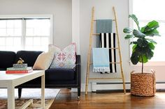 DIY Projects to Organize Your Home in Style | eHow/ A bamboo ladder is a chic decorative accent that doubles as a versatile vertical organizer. Use it to display pretty blankets in your living room, nice towels in your bathroom, or inspirational magazines in your creative workspace. The best part (aside from being able to use it in any room)? You can make it for under $20.