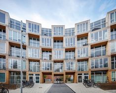 The apartment takes the form of a singular prefab structure. Tagged: Exterior, Wood Siding Material, Apartment Building Type, and Flat RoofLine. Photo 5 of 15 in This Curving Prefab Building in Copenhagen Contains 66 Affordable Apartments. Social Housing Architecture, World Architecture Festival, Modern Architecture, Big Architects, Famous Architects, Prefab Buildings, Modular Housing, Low Cost Housing, Timber Structure