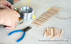 Make a simple DIY fairy garden fence with popsicle sticks and wire.