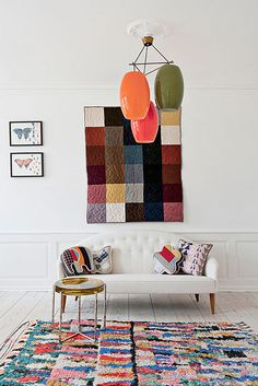 {wall hanging, pillows, ceiling lamp} add touches of colour to an otherwise white room for full impact! :)