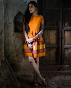 This box pleated mango-orange dress has been crafted from a handwoven tribal Rabari shawl fresh off the loom from Bhujodi Village in Kutch, India. This shawl ta Indian Fashion Trends, Indian Designer Outfits, Indian Outfits, Designer Dresses, Ethnic Trends, Kurta Designs, Blouse Designs, Sari Dress, Wool Dress