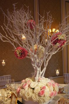 A very unique centerpiece with pomanders hanging on the branches. Such a classy wedding! By Design Works in Denver