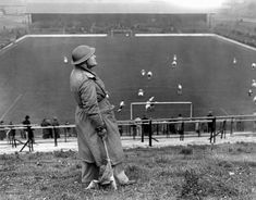 An air-raid 'spotter' watches the skies as Charlton Athletic take on Arsenal at The Valley in the background, 1939
