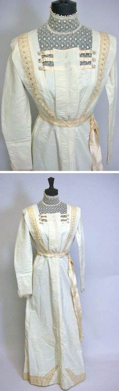 Cream day dress, ca. 1912, with a high neck and long sleeves. Lace panel in bodice front and at hemline and cuffs. Cream satin evening skirt. Brightwells