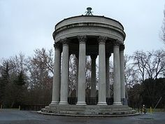 Sunol Water Temple | Sunol, CA | Open air round, marble structure resting on a layered base with twelve columns supporting the round, marble roof. There are leafless trees i...