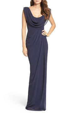 This fluid gown with an elegantly draped cowl neckline is cinched at the waist and finished with a flowing skirt with a partial train.