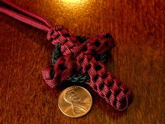Maroon crown sinnet paracord cross with Celtic ring.  A long 4 bight Turk's head knot was tied with 0.9mm black cord over a key/split ring, then the cross was tied around it.