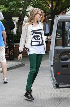 Cara Delevingne Casually Dressed In Printed Tee, A Lacey Letterman Jacket, Green Skinnies, Studded High-Tops. Cara Style.
