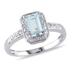 Express your love with this elegant Aquamarine and Diamond Halo Ring. Crafted in lustrous white gold, this ring features an emerald-cut (7mm x 5mm) aquamarine gemstone and 14 round-cut, pave-set diamond accents (G-H, I2-I3) shimmering along the band.