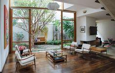 Assinado pelo arquiteto Jorge Siemsen, o projeto da casa foi pensado em torno de uma jabuticabeira que já existia no terreno. A sala, de pé-direito duplo, tem portas de vidro que integram ambientes interno e externo