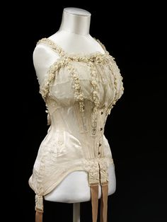 Wedding corset, satin, machine made lace and artificial orange blossom. Worn by Mrs G. E. Dixon, Uk, 1905