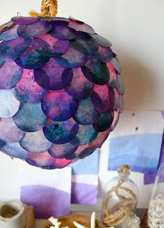 Fish scale lamp, which can be made in an afternoon!  The materials needed are a white paper globe lantern,paper circle cutter, Dye, paraffin wax, mineral oil, crock pot, extra bowl & a glue gun.   definitely making this!