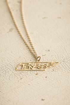 You'll find that the saying Follow Me To Tennessee might have a positive effect on your day when you wear this nicely-crafted graphic state necklace made of recycled brass and available in sterling si