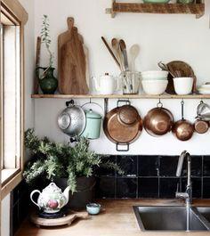 .pots hanging under shelf, bowls and utensils, boards etc on shelf