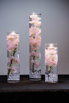 This Table Setting will include the following : 1 - 20 x 4 Cylinder Vase 1- 14 x 4 Cylinder Vase 1- 12 x 4 Cylinder Vase 3-Pink Cherry Blossom Silk Floral Strands (not real silk) Or white -- Choose from the drop down 3- Floating Candles 1- Bag of Acrylic Crystals For More Floral Water