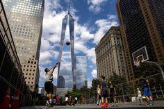 One World Trade Center towers over lower Manhattan as children play basketball in New York. - Brendan McDermid/Reuters
